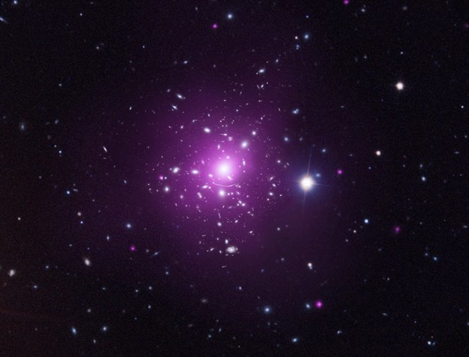 <p><strong>Figure 1:</strong> A composite optical and X-ray image of Abell 383, one of the 7 relaxed rich clusters considered in the study by Newman et al. 2013a,b. This image shows the X-ray emission of the hot electron gas in the cluster (in purple), its member galaxies and its central Brightest Cluster Galaxy which exhibits an extended diffuse envelope of stars around it.</p>