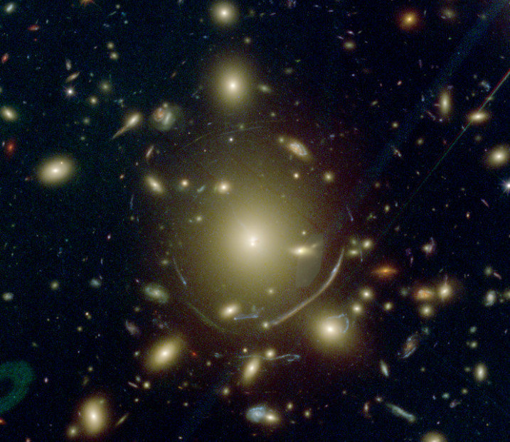 <p><strong>Figure 2:</strong> A zoom on the BCG in Abell 383 taken with the Hubble Space Telescope. The central BCG is surrounded by an extended envelope of stars and the numerous distorted images around it are background galaxies which are getting lensed by the cluster. Because of their high masses, galaxy clusters can act as gravitational lenses: the background galaxies close to the line of sight of the cluster get multiply imaged or distorted into large arcs like the one visible south of the BCG. Some of the cluster galaxies (e.g. the bright elliptical galaxy one on the south-east of the BCG) act as additional lenses which further distort some of the multiple images.<em><br /></em></p>