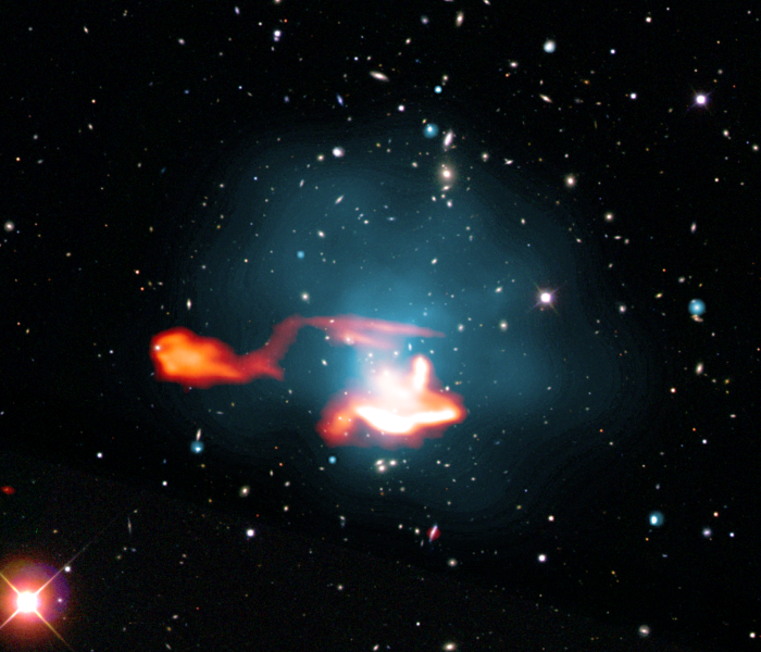 "False colour image of the galaxy cluster Abell 1033, consisting of a superposition of images in the radio, X-ray and optical frequency range. The radio galaxy with its tail appears as an orange, luminous, outward-directed structure in the left part of the picture. Its tail extends to the right into the upper part of the centre of the cluster of galaxies; as the gas emits X-rays there, it is shown here in blue. This tail was made to shine again by processes in the cluster of galaxies. The bright source in the lower part of the cluster is presumably independent and has also been classified as a re-iluminated radio tail of another galaxy, i. e. another ""radio phoenix""."